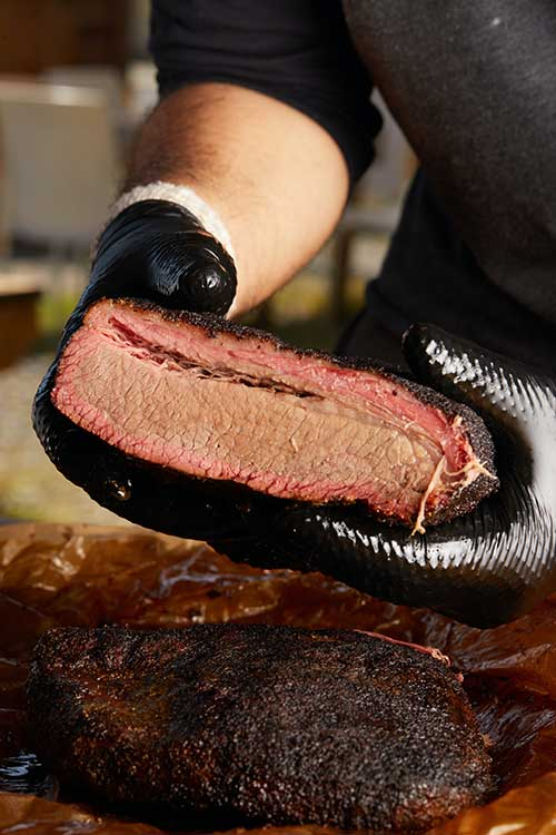 Jose Mier shows smoke ring on brisket in Sun Valley